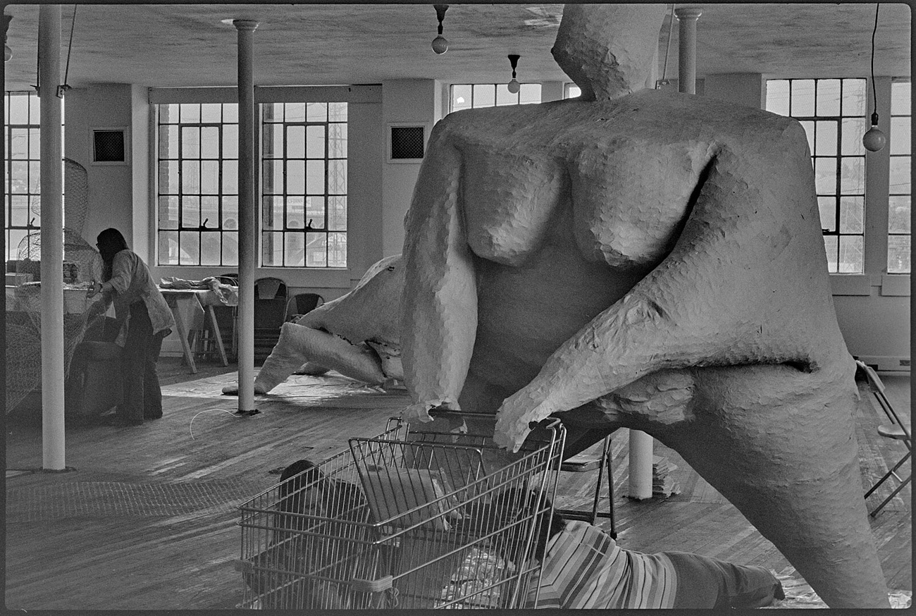 Large sculpture of nude woman with hands on a shopping cart. Two people lie on floor working on a leg.