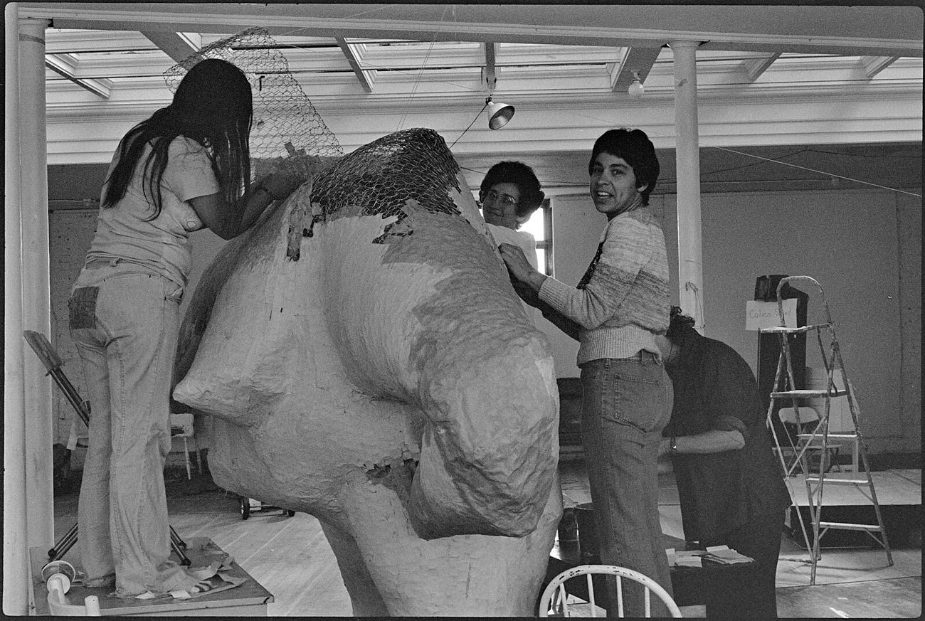 Four women work on body of large sculpture