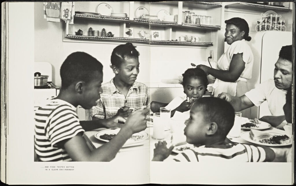 """A two-page spread of a book, featuring a black and white photograph of a Black family seated around a dinner table. The mother is standing back right looking at her family seated closer to the camera. The image crosses the book's gutter, taking up most of the two pages. A small caption bottom left reads, """"And food tastes better in a clean environment."""""""