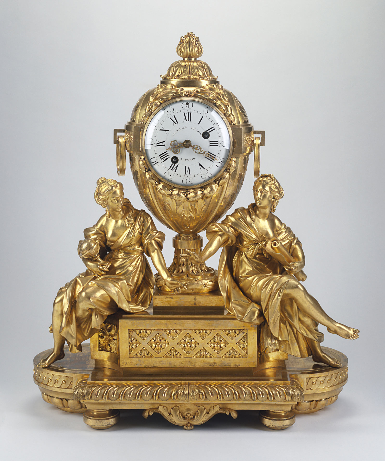 Golden clock on a foundation of two box plateaus, with female figures sitting on either side