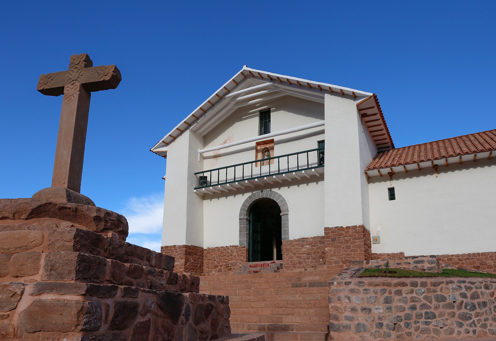 Small white church with a steepled two story entrance, and a terra cotta or sandstone cross out front
