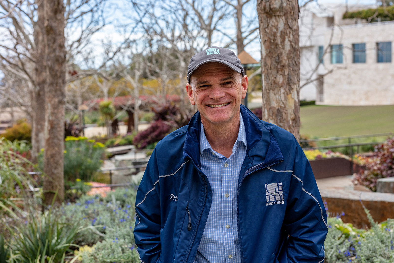 Brian Houck wears a cap and blue jacket, looking at the camera. Behind him are trees