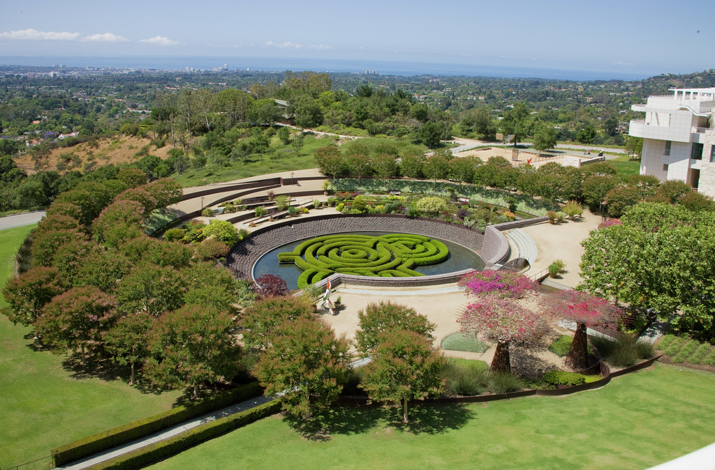 Expansive view from above of the circular Central Garden. The ocean is visible in the distance.