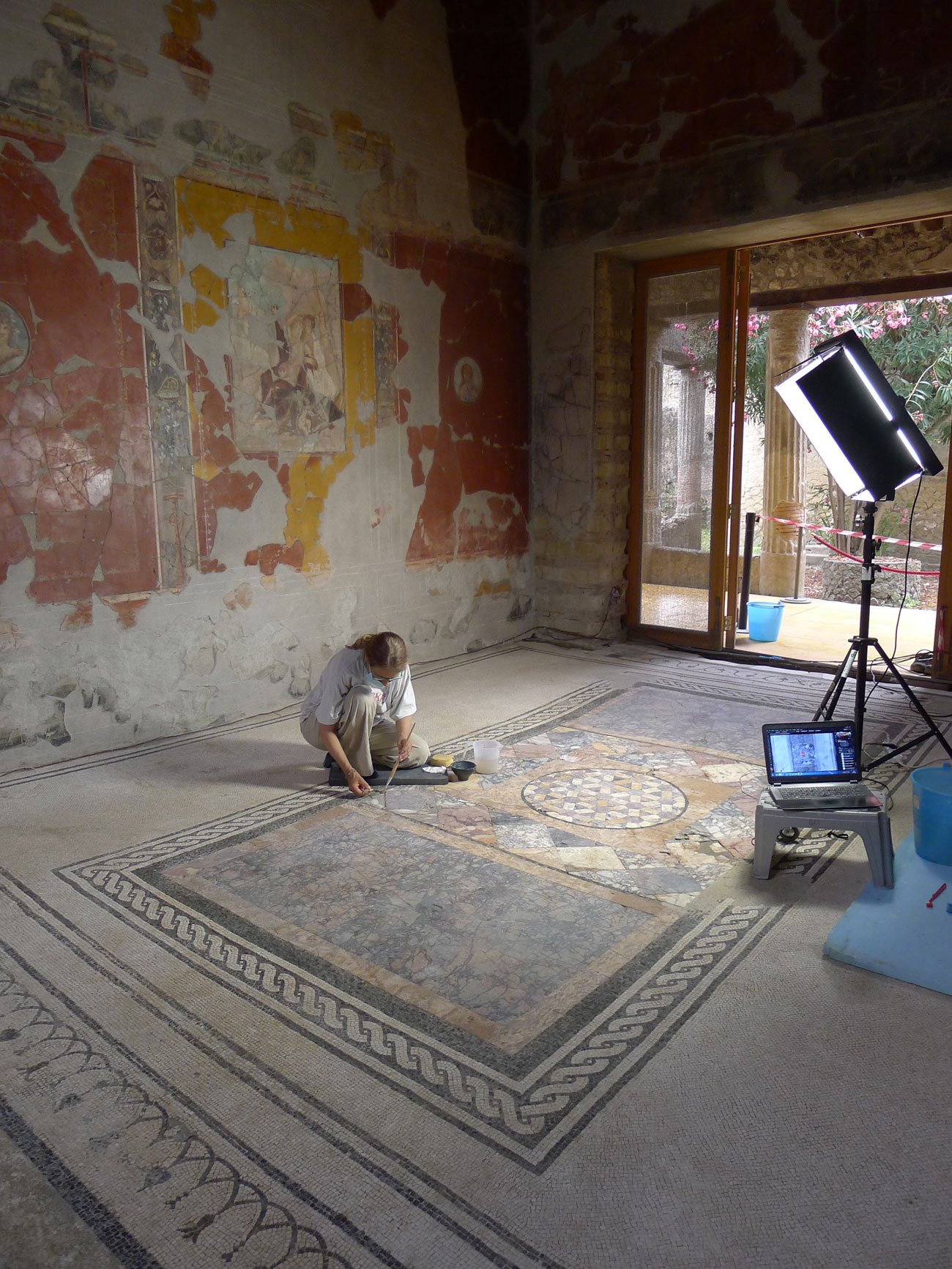 A woman kneels on the mosaic floor of a room in an ancient house with peeling paint on the walls, and a laptop computer and large light on the floor face her