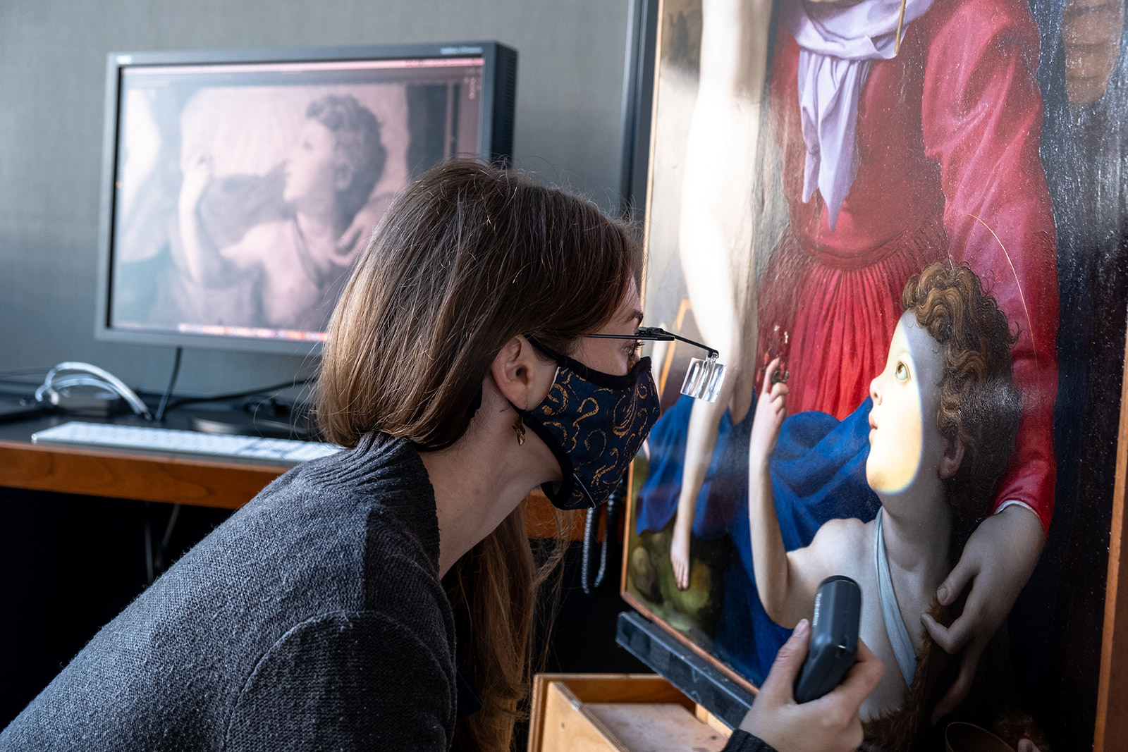 Woman wearing a face mask and glasses with magnification looks closely at a painting of a woman wearing red dress and child with curly hair