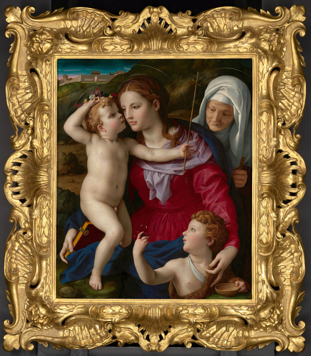 Elaborate gold frame around painting of woman holding two toddlers with an older woman peering over her shoulder