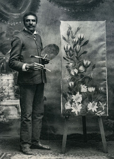 Man holding paintbrushes and a palette standing next to a tall painting of white flowers propped on an easel