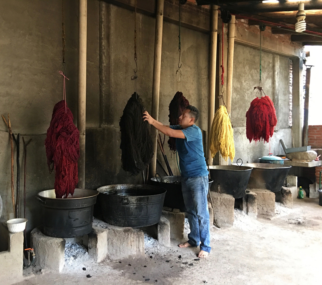 Man standing in large open space with clumps of yarn in different colors hanging over large tubs