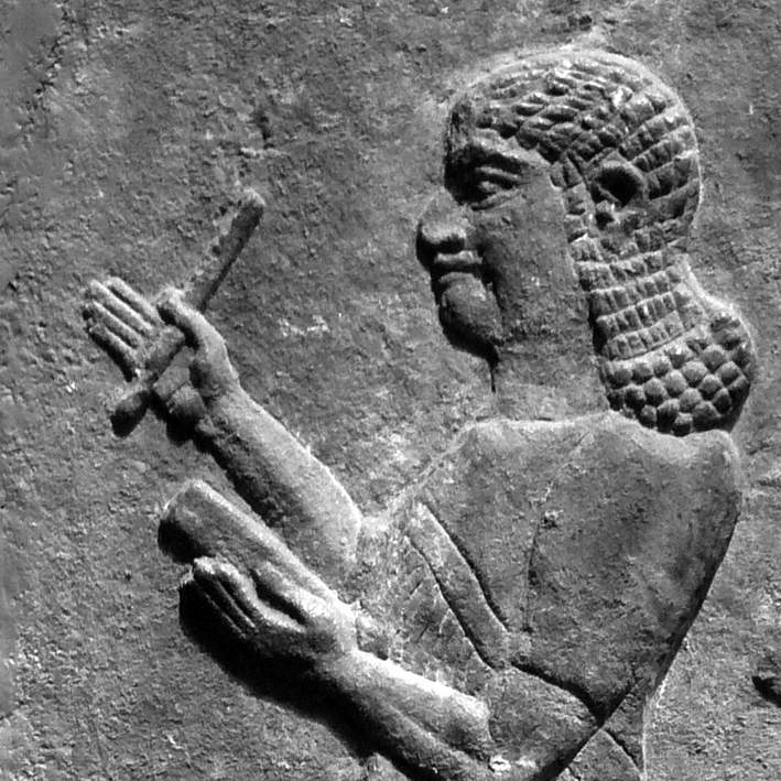 Piece of gray stone featuring image of man holding stylus and tablet etched into it