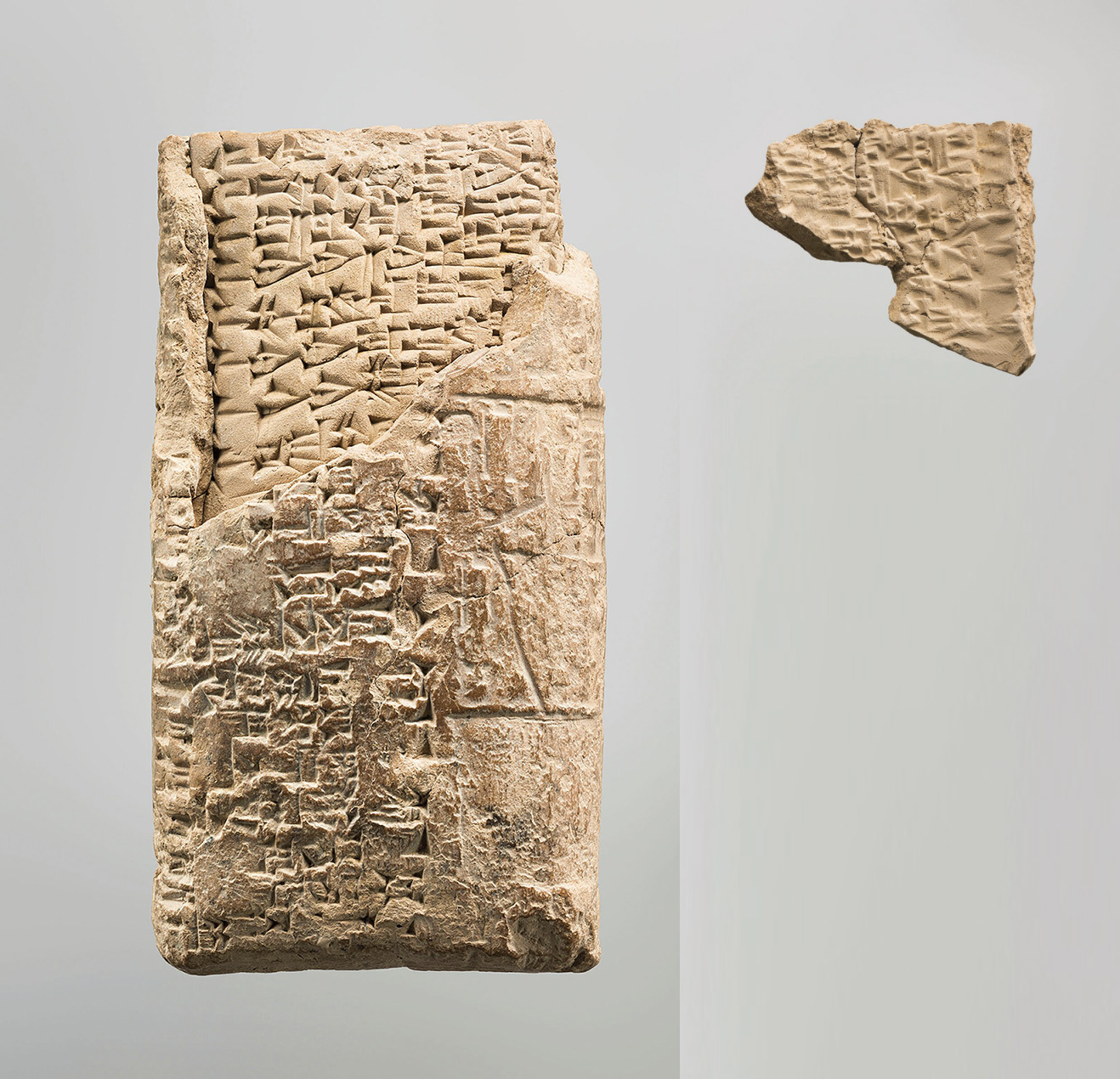 Whitish gray colored piece of clay in the shape of a rectangular envelope, with inscriptions etched into the clay and a corner broken off