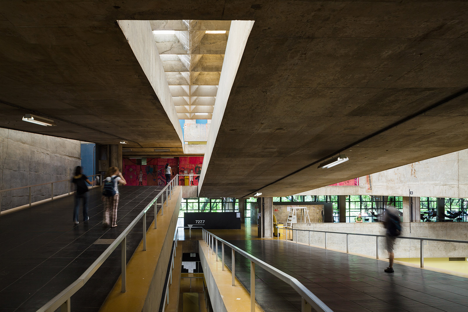 Interior of concrete building with two parallel ramps leading to different levels. People walking on the ramps are blurred.