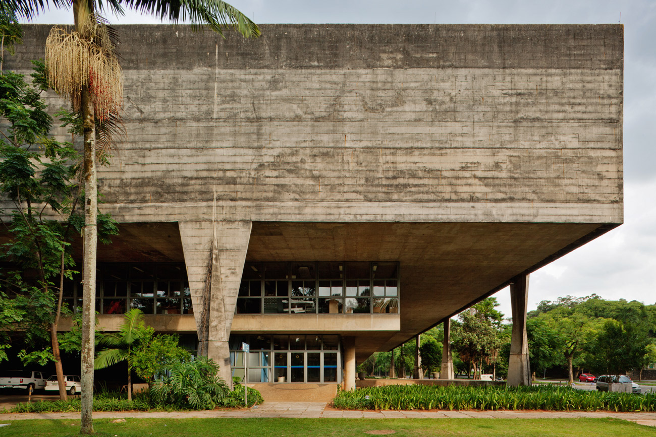 Large concrete building with two floors covered in windows, topped with a thick concrete roof supported by columns