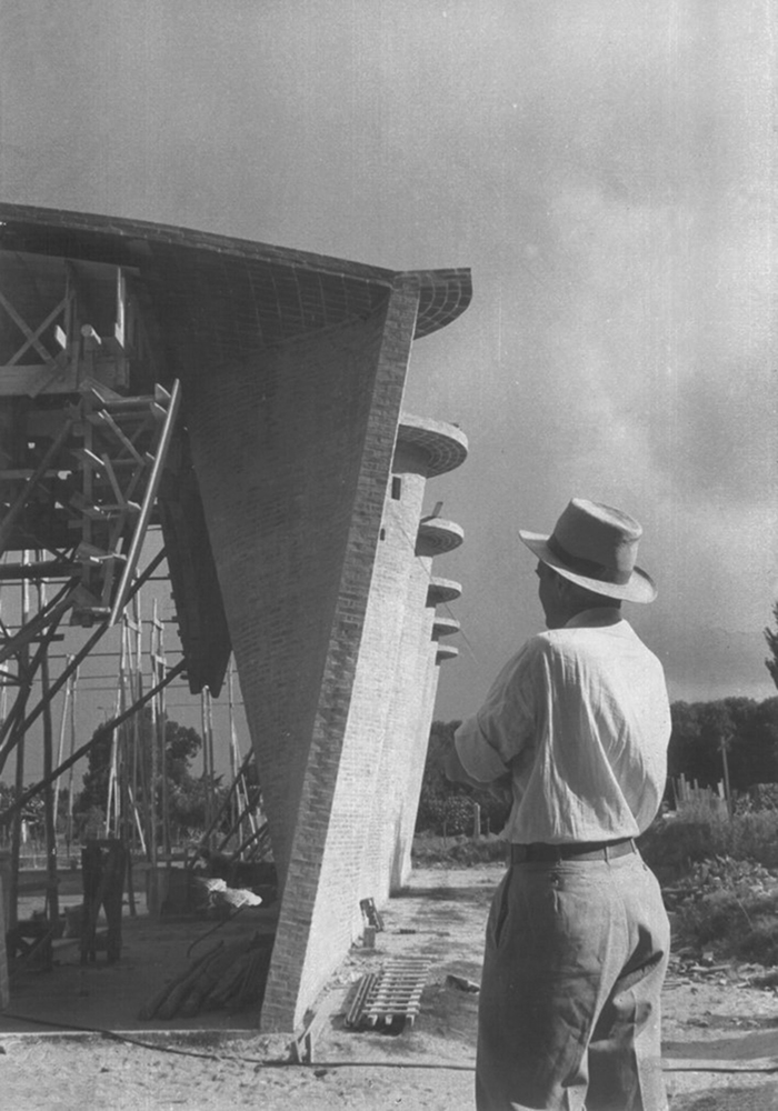 Black and white photograph of the Cristo Obrero church under construction, as the architect looks at it with his back to the camera