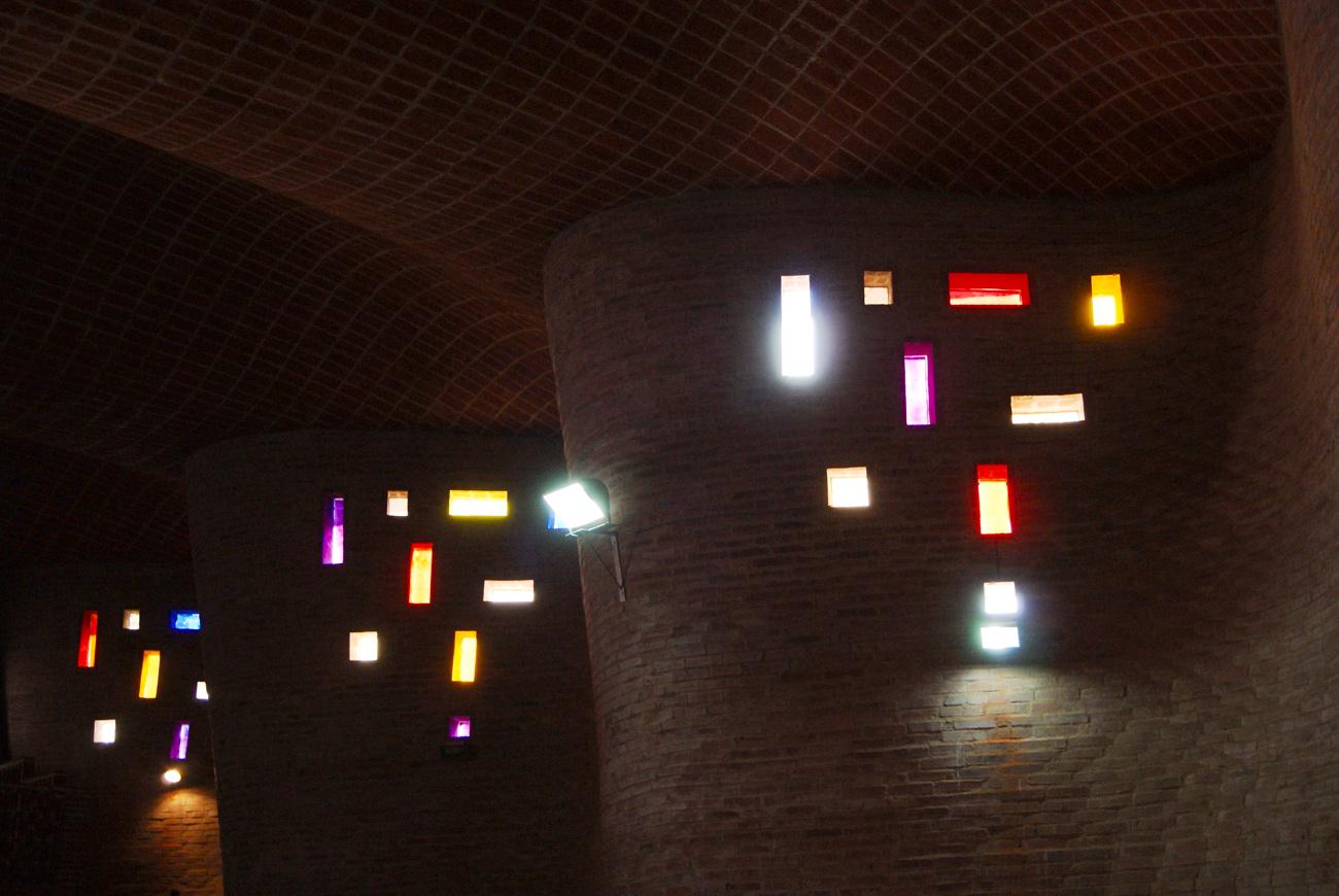 Interior view of Cristo Obrero with multi colored lights shining through the windows