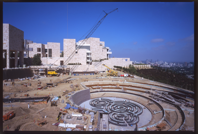 Color photo of Getty Central Garden under construction, so the ground is brown dirt and the museum sits in the background