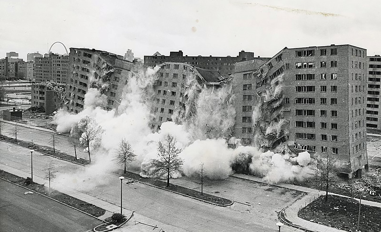 Tall buildings photographed in the midst of demolition, surrounded by billowing smoke.