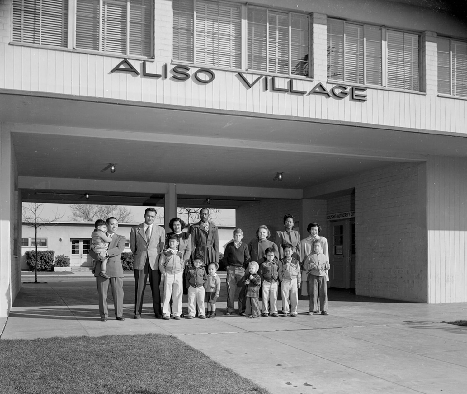 Families pose in front of the Aliso Village apartment complex.